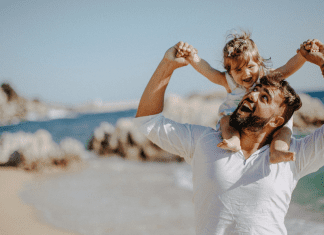 father holding young daughter on his shoulders at the beach